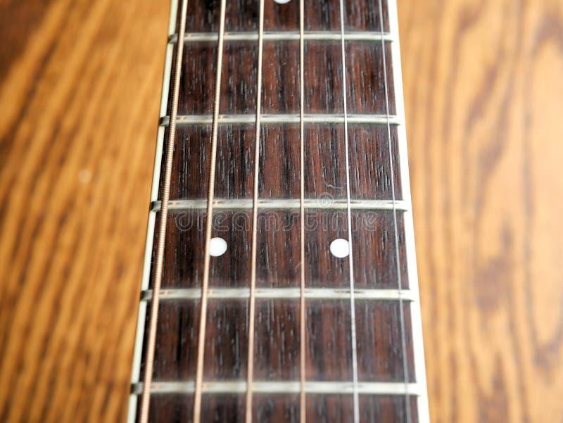 Ακουστικός ξύλινος στενός επάνω κιθάρων στο ξύλινο υπόβαθρο με το fretboard, τις σειρές, και τους δέκτες για τη μουσική blogs, κο στοκ εικόνες με δικαίωμα ελεύθερης χρήσης