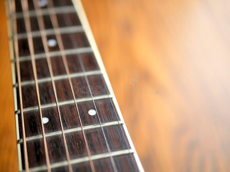 Ακουστικός ξύλινος στενός επάνω κιθάρων στο ξύλινο υπόβαθρο με το fretboard, τις σειρές, και τους δέκτες για τη μουσική blogs, κο στοκ φωτογραφίες