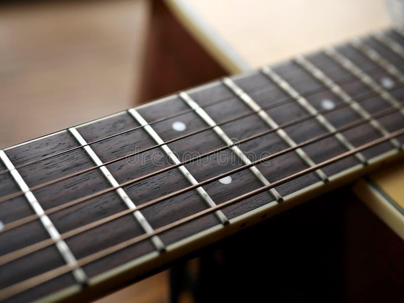 Ακουστικός ξύλινος στενός επάνω κιθάρων στο ξύλινο υπόβαθρο με το fretboard, τις σειρές, και τους δέκτες για τη μουσική blogs, εμ στοκ φωτογραφίες με δικαίωμα ελεύθερης χρήσης