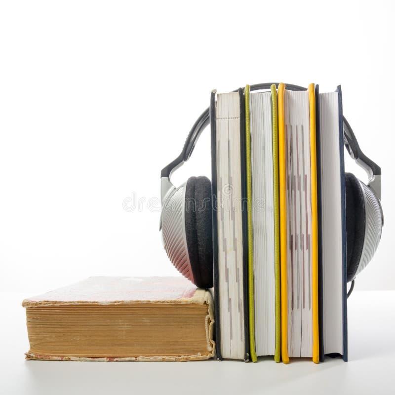 Ακουστικός σωρός βιβλίων των βιβλίων βιβλίων με σκληρό εξώφυλλο και του ηλεκτρονικού αναγνώστη ηλεκτρονική βιβλιοθήκη έννοιας πίσ στοκ εικόνα με δικαίωμα ελεύθερης χρήσης