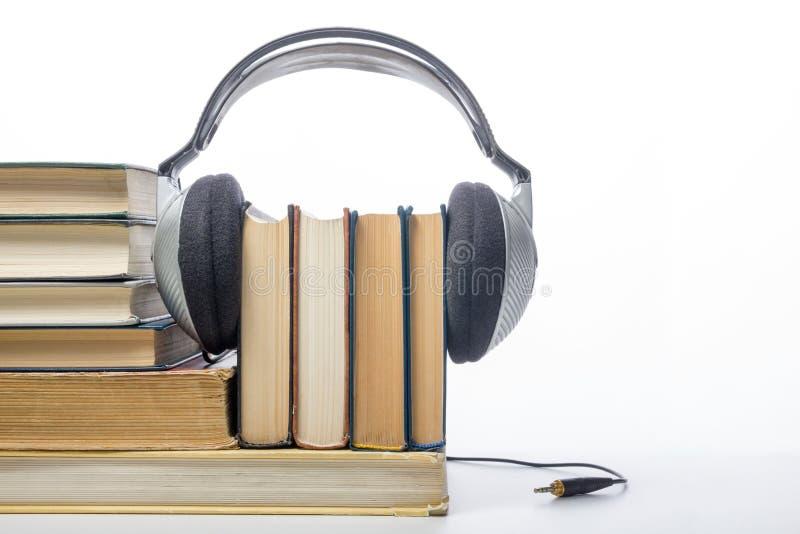Ακουστικός σωρός βιβλίων των βιβλίων βιβλίων με σκληρό εξώφυλλο και του ηλεκτρονικού αναγνώστη ηλεκτρονική βιβλιοθήκη έννοιας πίσ στοκ φωτογραφία με δικαίωμα ελεύθερης χρήσης