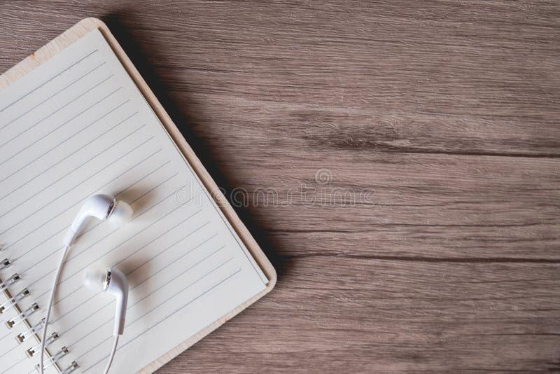 Ακουστικό στο κενό όφελος στον ξύλινο πίνακα, διάστημα αντιγράφων στοκ φωτογραφία