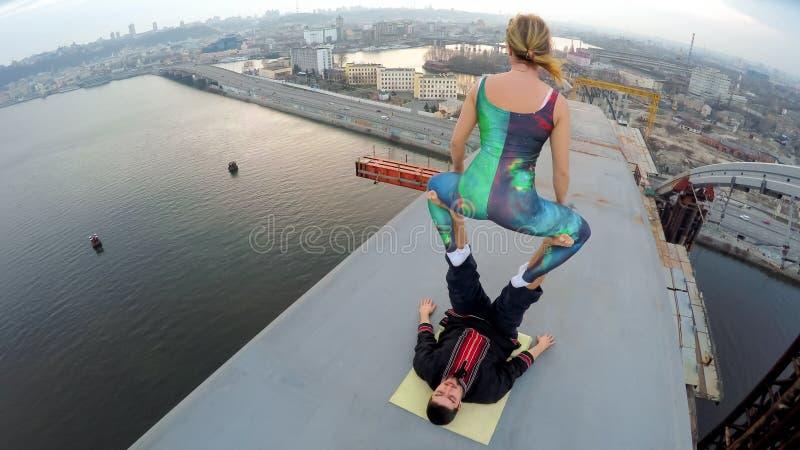 Ακραίος αθλητισμός, θηλυκή εξισορρόπηση στα αρσενικά πόδια πάνω από τη γέφυρα, επικίνδυνο χόμπι στοκ φωτογραφίες με δικαίωμα ελεύθερης χρήσης