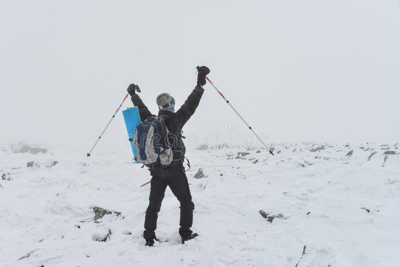 ακραίος αθλητισμός Απομονωμένος οδοιπόρος στα χειμερινά βουνά που στέκονται στην αιχμή με αυξημένος επάνω hads στοκ φωτογραφία