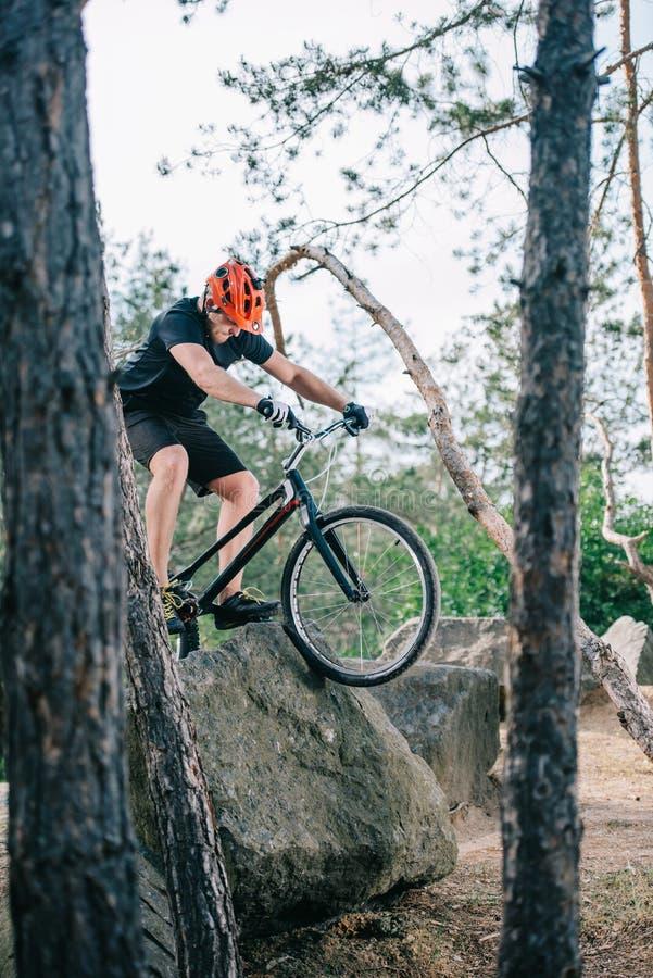 ακραίος νέος δοκιμαστικός ποδηλάτης που αναρριχείται στο βράχο στοκ εικόνα