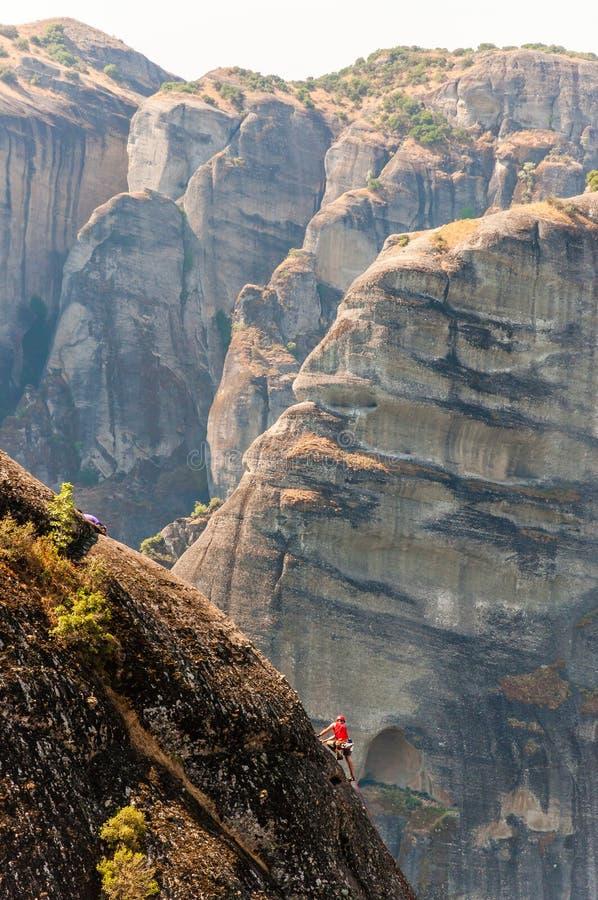 Ακραίος ορειβάτης βράχου που αναρριχείται στην αιχμή ένας από τους απότομους βράχους σχηματισμών βράχου Meteora στοκ εικόνα με δικαίωμα ελεύθερης χρήσης