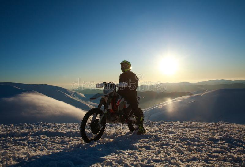 Ακραίος ποδηλάτης στην αθλητική μοτοσικλέτα στο βουνό χειμερινού χιονιού στον ουρανό στοκ εικόνες