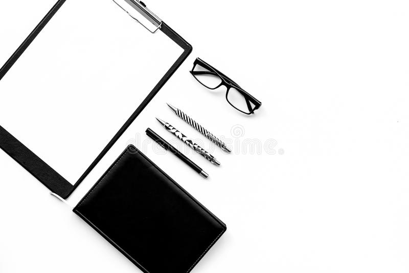 Ακριβής μονοχρωματικός άσπρος και μαύρος πίνακας γραφείων γραφείων με το μαξιλάρι, χαρτικά, σημειωματάριο, γυαλιά στην άσπρη τοπ  στοκ φωτογραφία