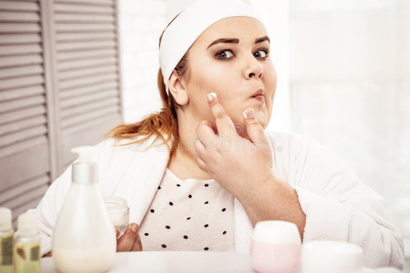 Ακριβής συγκεντρωμένη μεγάλη κυρία που προετοιμάζει το δέρμα της για τη μακριά ημέρα στοκ εικόνα