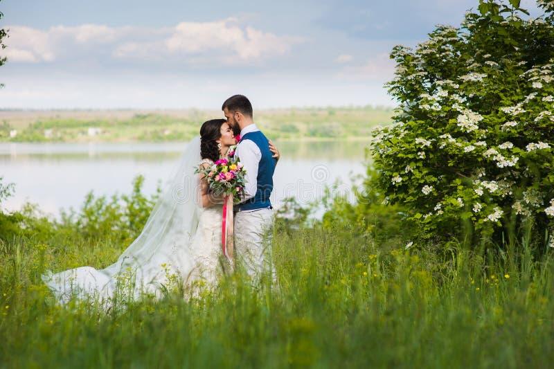 Ακριβώς παντρεμένο ζευγάρι στο landcape με το νερό στοκ εικόνα