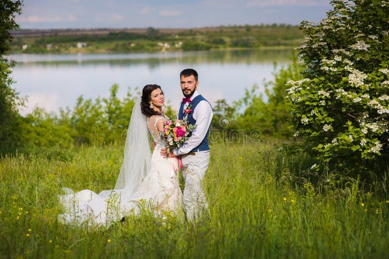 Ακριβώς παντρεμένο ζευγάρι στο landcape με το νερό στοκ εικόνες