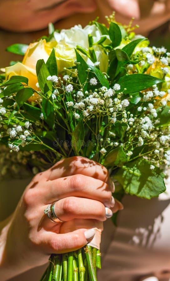 Ακριβώς παντρεμένο νέο ζευγάρι με την ανθοδέσμη των λουλουδιών στοκ εικόνες