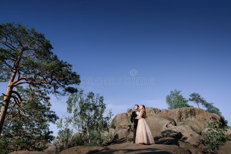 Ακριβώς το παντρεμένο ζευγάρι εξετάζει το λάμποντας ήλιο που στέκεται στους βράχους στοκ εικόνα με δικαίωμα ελεύθερης χρήσης