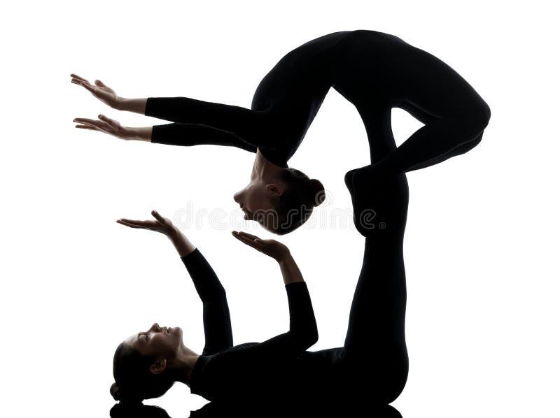 Ακροβάτης δύο γυναικών που ασκεί τη γυμναστική σκιαγραφία γιόγκας στοκ εικόνες