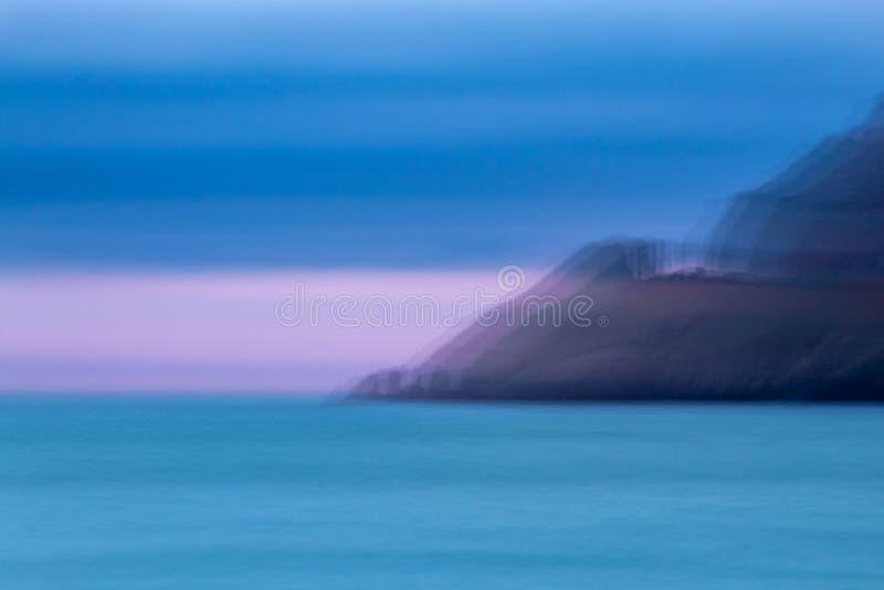 Ακρωτήριο Artisitic που έρχεται κάτω στη θάλασσα στο ηλιοβασίλεμα στοκ εικόνες