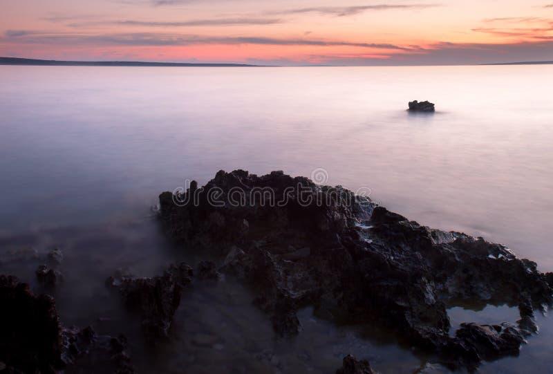Ακτή ηλιοβασιλέματος με το βράχο στοκ φωτογραφίες με δικαίωμα ελεύθερης χρήσης