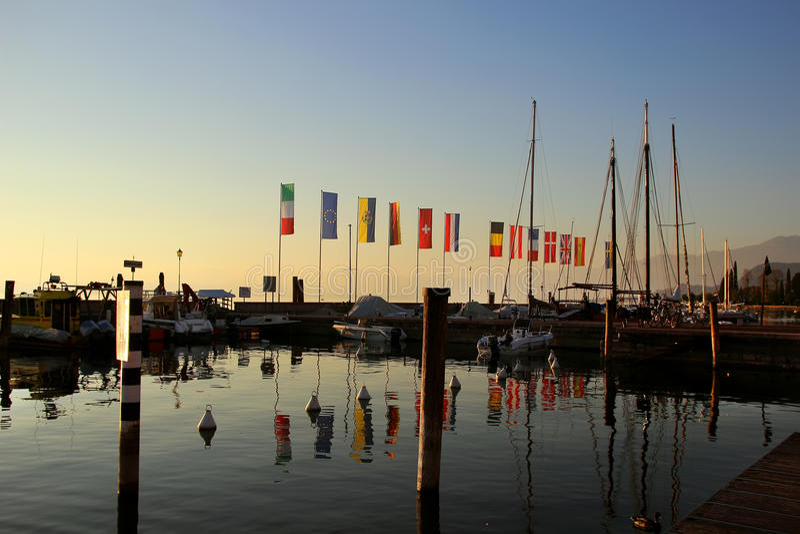 Ακτή με τα κοντάρια σημαίας και τις βάρκες στοκ φωτογραφίες