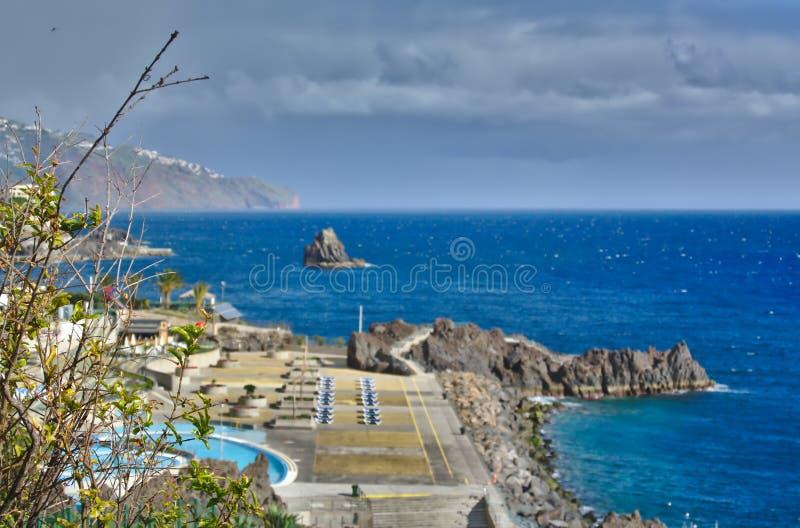 Ακτή της Μαδέρας ` s το φθινόπωρο μια φωτεινή ημέρα με τον τίτλο σύννεφων προς το νησί στοκ εικόνες