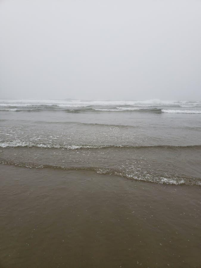 Ακτή του Όρεγκον που βρέχει πάντα επειδή τα κύματα εδάφους ποτέ πίσω στη θάλασσα στοκ φωτογραφία