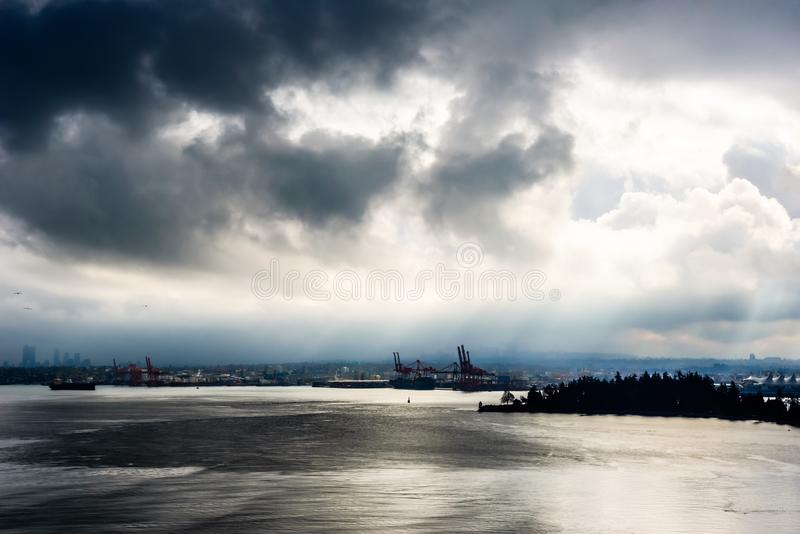 Ακτίνες ήλιων και σκοτεινά σύννεφα πέρα από την πόλη και το νερό στοκ φωτογραφία