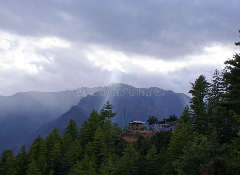 Ακτίνες του ελαφριού ραγίσματος ήλιων μέσω των σύννεφων επάνω στις αιχμές βουνών στοκ εικόνες με δικαίωμα ελεύθερης χρήσης