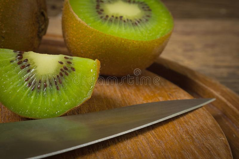 Ακτινίδιο Τεμαχισμένος μισός φρέσκος τέμνων πίνακας με το μαχαίρι στο παλαιό ξύλο στοκ εικόνα