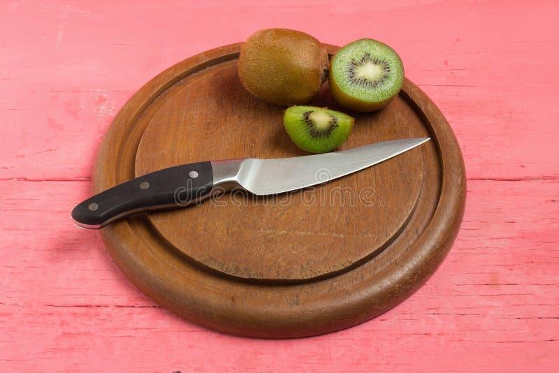 Ακτινίδιο Τεμαχισμένος μισός φρέσκος τέμνων πίνακας με το μαχαίρι στο παλαιό ξύλο στοκ φωτογραφία με δικαίωμα ελεύθερης χρήσης