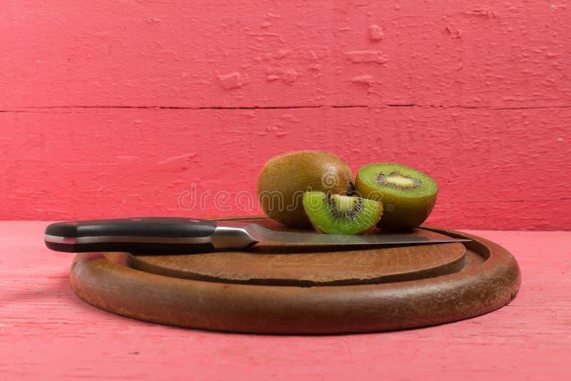 Ακτινίδιο Τεμαχισμένος μισός φρέσκος τέμνων πίνακας με το μαχαίρι στο παλαιό ξύλο στοκ φωτογραφίες με δικαίωμα ελεύθερης χρήσης