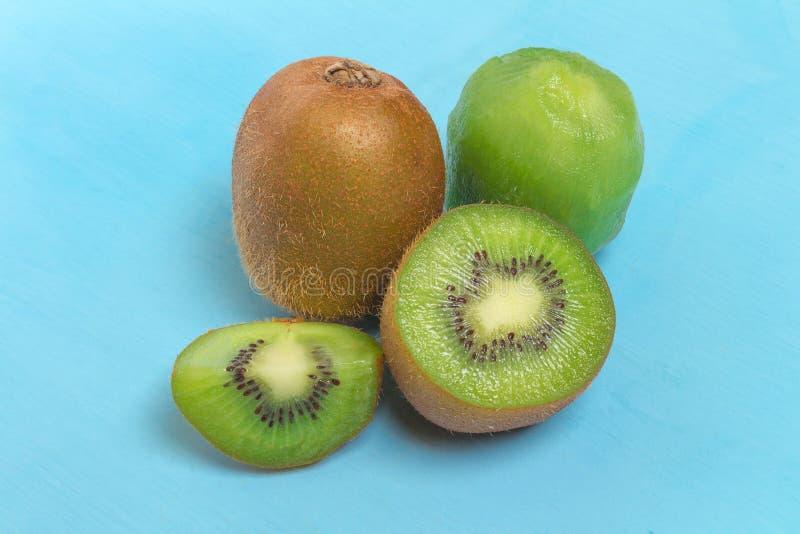 Ακτινίδιο Τεμαχισμένος μισός φρέσκος φρούτα στο παλαιό ξύλινο μπλε στοκ φωτογραφία