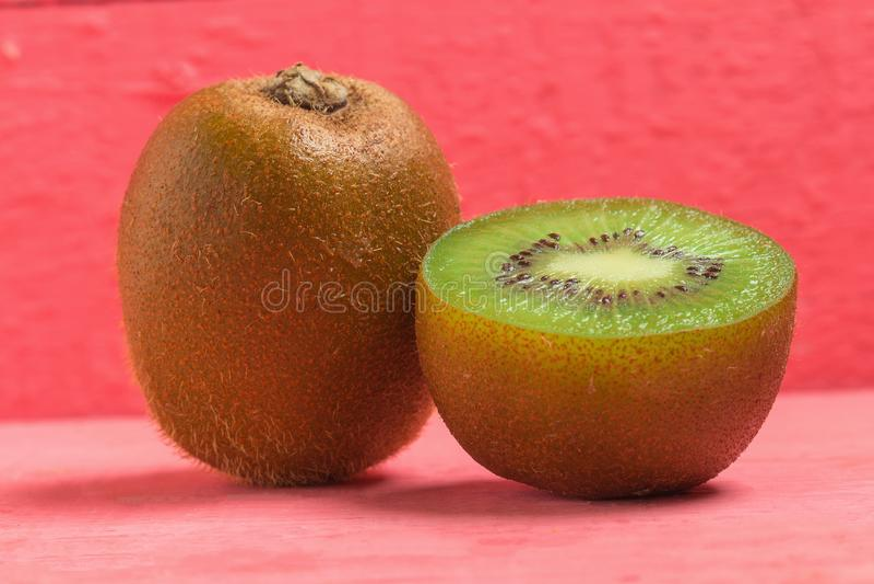 Ακτινίδιο Τεμαχισμένος μισός φρέσκος φρούτα στο παλαιό ξύλινο ροζ στοκ φωτογραφίες