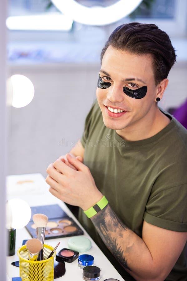 Ακτινοβολία του σκοτεινός-μαλλιαρού τακτοποιημένου τύπου που μεταχειρίζεται το πρόσωπό του με τα προϊόντα skincare στοκ εικόνες