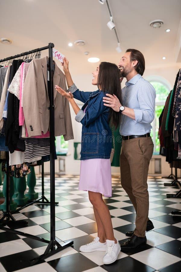 Ακτινοβολώντας άτομο που εξετάζει το νέο σακάκι με την ετικέττα πώλησης στοκ φωτογραφίες