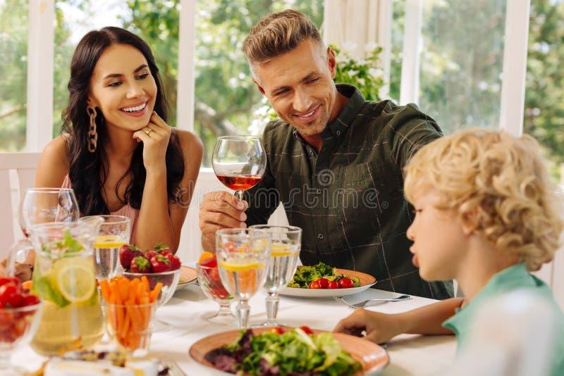 Ακτινοβολώντας γονείς που χαμογελούν ακούοντας το χαριτωμένο έξυπνο γιο τους στοκ εικόνες