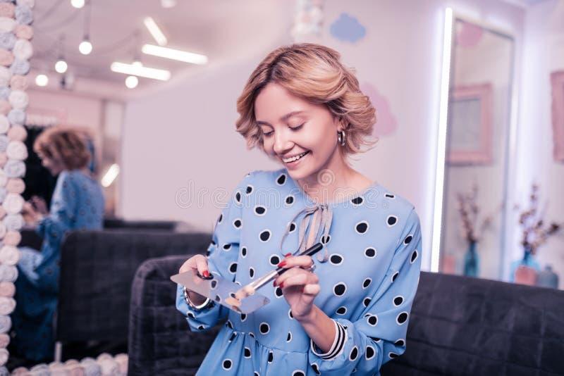 Ακτινοβολώντας γυναίκα που χαμογελά πρίν χρησιμοποιεί το ίδρυμα το πρωί στοκ φωτογραφία με δικαίωμα ελεύθερης χρήσης