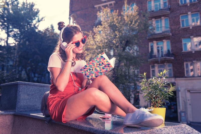 Ακτινοβολώντας κορίτσι που ονειρεύεται την ύπαρξη σχεδιαστής μόδας που διαβάζει το μοντέρνο περιοδικό στοκ φωτογραφίες