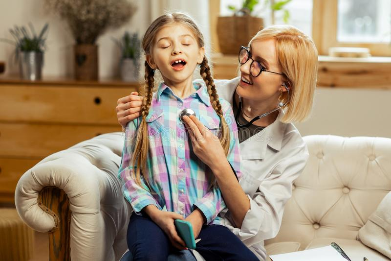 Ακτινοβολώντας παιδίατρος που εξετάζει τους πνεύμονες του άρρωστου κ στοκ εικόνες