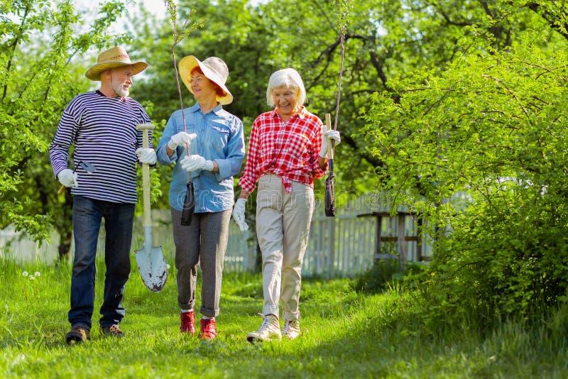 Ακτινοβολώντας συνταξιούχοι που περπατούν με το βόστρυχο και τα φτυάρια πρίν φυτεύει τους στοκ εικόνα με δικαίωμα ελεύθερης χρήσης