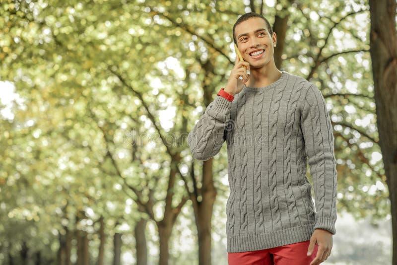 Ακτινοβολώντας τον σκοτεινός-μαλλιαρό τύπο στα κόκκινα εσώρουχα που έχουν το τηλεφώνημα στοκ φωτογραφία