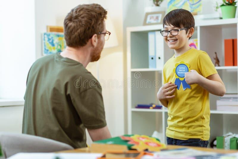 Ακτινοβολώντας το νέο αγόρι στα σαφή γυαλιά που είναι υπερήφανα του φωτεινού σημαδιού στοκ φωτογραφία με δικαίωμα ελεύθερης χρήσης
