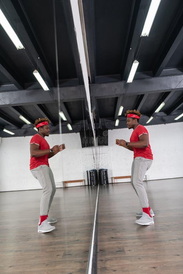 Ακτινοβολώντας το σκοτεινός-μαλλιαρό ενεργό άτομο που έχει τη διασκέδαση χορεύοντας στοκ φωτογραφίες