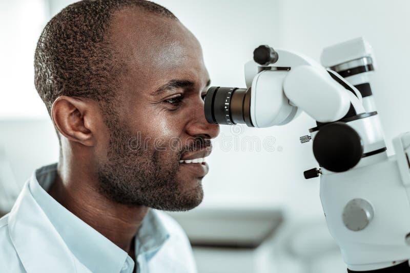 Ακτινοβολώντας stomatologist αφροαμερικάνων που εργάζεται ενεργά με το μικροσκόπιο στοκ φωτογραφία με δικαίωμα ελεύθερης χρήσης