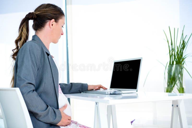 δακτυλογράφηση γυναικών pregnantbusiness στο lap-top της στοκ φωτογραφία με δικαίωμα ελεύθερης χρήσης