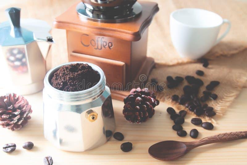 Ακόμα επίγειος καφές ζωής στο δοχείο καφέ, τον εκλεκτής ποιότητας μύλο καφέ και τα φασόλια καφέ στον πίνακα στοκ εικόνες