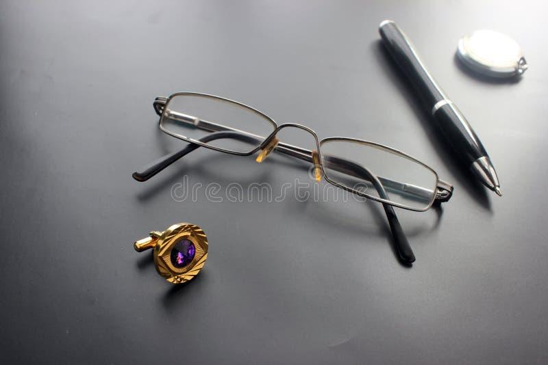 Ακόμα ζωή, επιχείρηση, προμήθειες γραφείων ή έννοια εκπαίδευσης: μια άποψη ξαπλωμένο να γεμίσει, γυαλιά, μια μάνδρα, ένα ρολόι, ε στοκ εικόνες