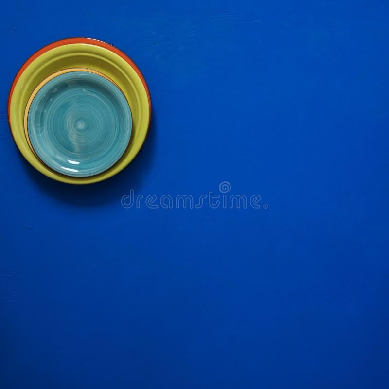 Ακόμα ζωή - λίγα ζωηρόχρωμα κενά πιάτα στέκονται στη γωνία του α στοκ φωτογραφίες