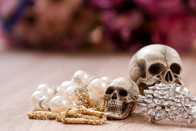 Ακόμα ζωή με ένα ανθρώπινο κρανίο με τον παλαιό χρυσό, το διαμάντι και το κόσμημα στοκ εικόνα