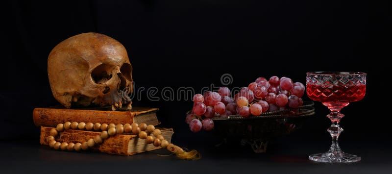 Ακόμα ζωή με ένα κρανίο, ένα βάζο των σταφυλιών και ένα ποτήρι του κόκκινου κρασιού στοκ εικόνες