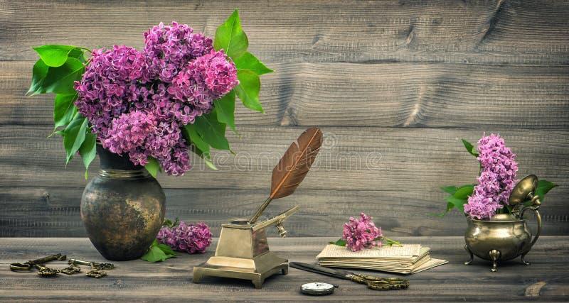 Ακόμα ζωή με τα ιώδη λουλούδια και τα παλαιά εργαλεία γραψίματος στοκ εικόνες