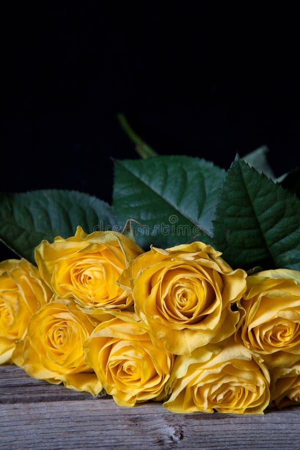 Ακόμα ζωή με τα κίτρινα μαραμένα τριαντάφυλλα στο μαύρο υπόβαθρο στοκ φωτογραφία με δικαίωμα ελεύθερης χρήσης