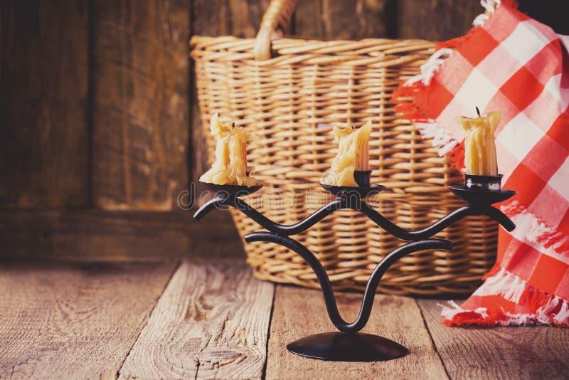 Ακόμα ζωή με τα κεριά, το ψάθινο καλάθι και την κόκκινος-ελεγχμένη πετσέτα στοκ φωτογραφία